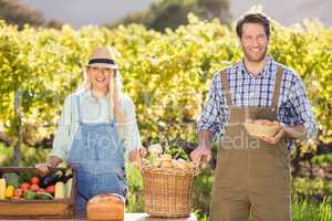 Happy farmer couple presenting their local food