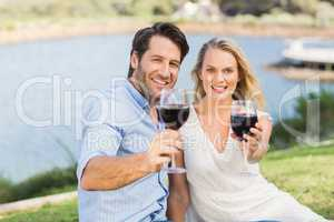 Cute couple on date handing red wine glasses