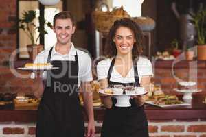 Smiling waiter and waitress showing plates with treat