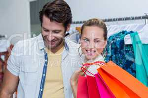 Smiling couple standing next to clothes rail