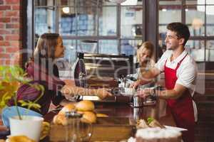 A smiling barista serving a client
