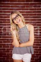 Gorgeous smiling blonde hipster playing with hair