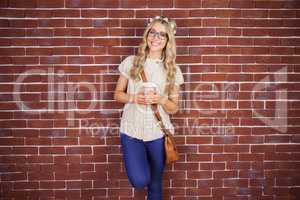 Gorgeous smiling blonde hipster leaning against red brick backgr