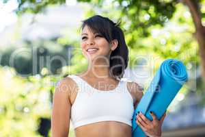 Smiling athletic woman carrying yoga mat