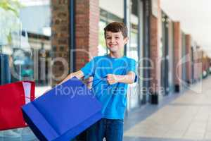 Young boy playing with shopping bags