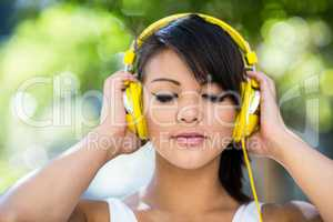 Athletic woman wearing yellow headphones and enjoying music with