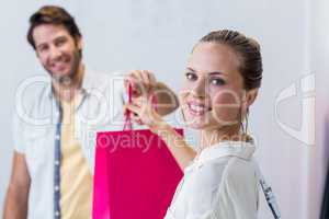 Smiling cashier giving shopping bag to woman