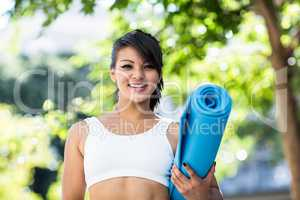 Portrait of smiling athletic woman carrying yoga mat