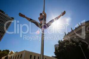 Athletic woman doing gymnastics on street sign