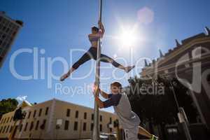 Extreme athletes hanging on street sign