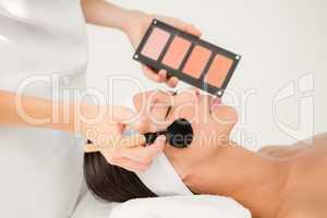 Hand applying makeup to beautiful woman