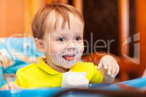Happy child dirty with cream yoghurt