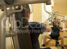 Mature man exercising on shoulder press machine