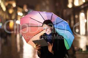 Woman using pad under umbrella in the evening city