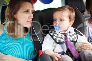 Mom looking at her son in child safety seat