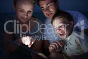 Parents and son with tablet PC outdoor late in the evening