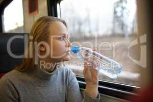Woman drinking water and looking out train window