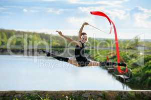 Gymnast girl doing leg-split in a jump with ribbon