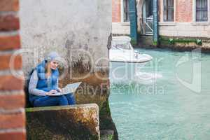 Young woman using laptop by the canal in Venice