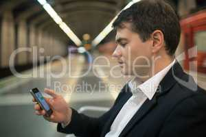Young man reading sms on smartphone in underground