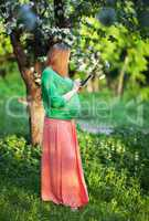Pregnant woman using tablet PC in green park