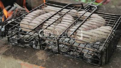 Grilled sausages over a fire at a picnic