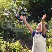 Boy playing catch soap bubbles outdoors