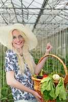 Hübsche Frau trägt einen Korb mit Gemüse auf dem Arm