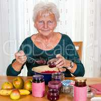 Senior woman filling homemade jam in the glass