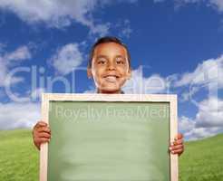 Happy Hispanic Boy In Grass Field Holding Blank Chalk Board