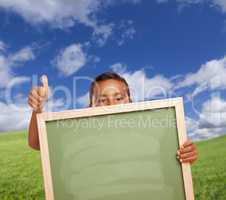 Boy with Thumbs Up in Field Holding Blank Chalk Board