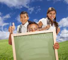 Hispanic Students with Thumbs Up in Grass Field Holding Blank Chalk Board.