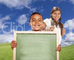 Hispanic Boy and Girl In Field Holding Blank Chalk Board