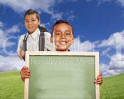 Happy Hispanic Boys In Grass Field Holding Blank Chalk Board