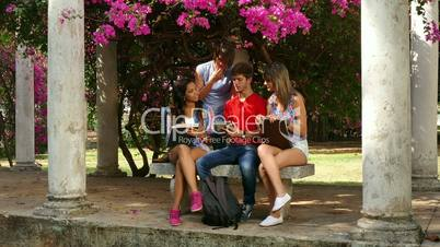 Young people, college students with books, school education, group of four friends in city park, teamwork. Boys and girls talking, studying and preparing homework for exam at university with ipad