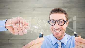 Composite image of geeky businessman holding two cables