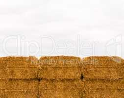Six stacked yellow hay bales on overcast sky