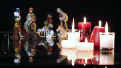 Christmas nativity scene with candles on black