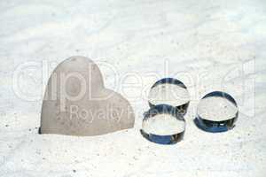 Großes Steinherz und drei Glaskugeln im Sand