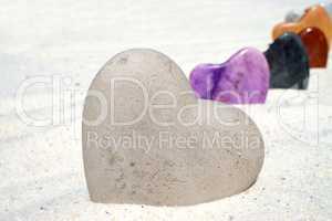 Großes Herz aus Stein steht im Sand