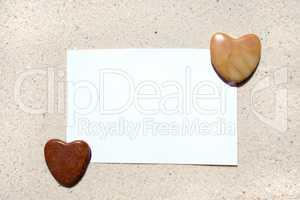 Weiße Postkarte mit Herzen am Strand