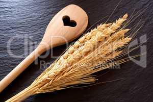 Holzlöffel und Getreideähren auf einer Schieferplatte