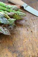 Grüner Spargel und Messer auf altem Holztisch