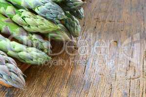 Grüner Spargel auf rustikalem Holztisch