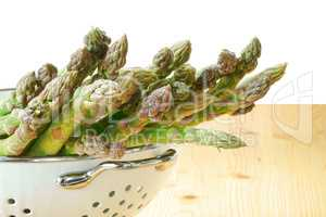 Grüner Spargel im Seiher auf Tisch vor weißem Hintergrund