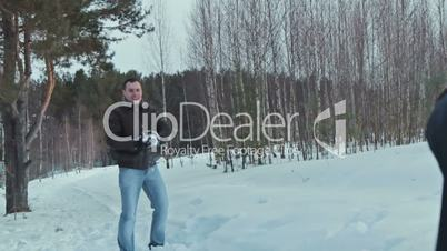 Couple having snowball fight in snow in winter forest, slowmotion