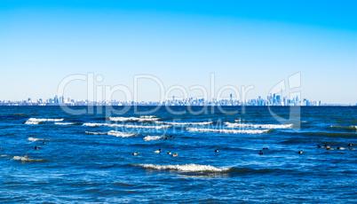 Waves breaking on lake with Toronto skyline on distant horizon