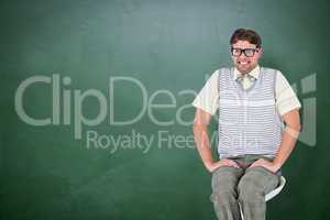 Composite image of geeky hipster sitting on stool