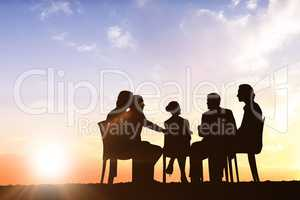 Composite image of silhouettes sitting