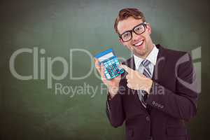 Composite image of geeky businessman pointing to calculator